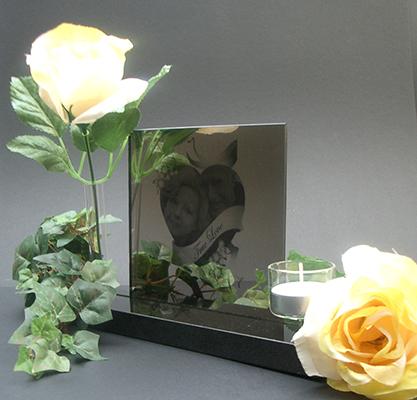 Fotolijst spiegel met gravure van de overleden persoon die geplaatst wordt in het midden van het hart. Voorzien van waxinelicht en vaasje voor een bloem. € 187,00